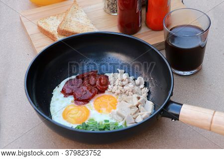 Indochina Pan Fried Egg With Toppings, Chinese Sausage And Pork Sausage In The Black Pan With Flavor