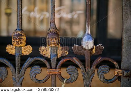 Head Of A Little Angel For Good Luck On A Decorative Lattice Near St. Bartholomew's Cathedral On The