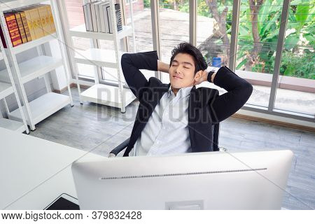 Asian Businessman In A Suit Sits Relaxed In Front Of A Computer, Stretches Arms,eyes Closed, And Lie
