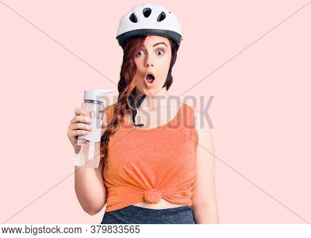 Young beautiful woman wearing bike helmet and holding water bottle scared and amazed with open mouth for surprise, disbelief face
