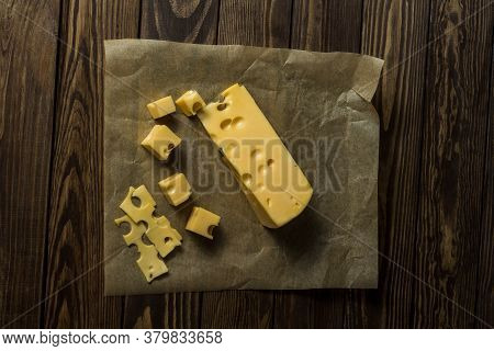 Maasdamer Cheese. Diced Cheese In Wrapping Paper On An Old Black Wooden Table. Food For Wine And Rom