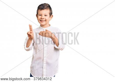 Cute blond kid wearing elegant shirt smiling swearing with hand on chest and fingers up, making a loyalty promise oath
