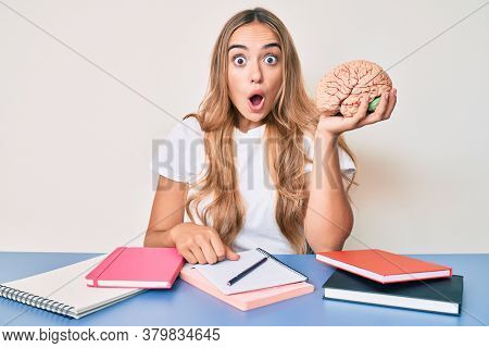 Young beautiful blonde woman holding brain while studying for school scared and amazed with open mouth for surprise, disbelief face