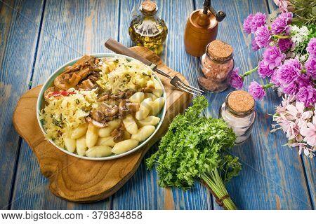 Braised Pork Loin With Mushrooms, Served With Silesian Dumplings And Sauerkraut Salad.