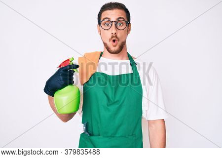 Young handsome man wearing apron holding sprayer scared and amazed with open mouth for surprise, disbelief face