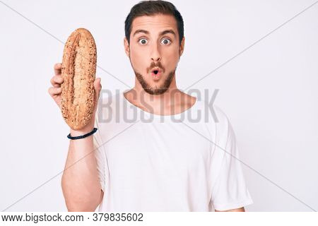 Young handsome man holding wholemeal bread scared and amazed with open mouth for surprise, disbelief face