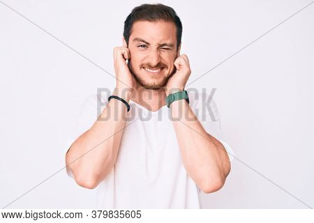 Young handsome man wearing casual white tshirt covering ears with fingers with annoyed expression for the noise of loud music. deaf concept.