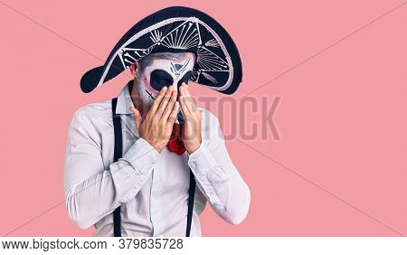 Man wearing day of the dead costume over background rubbing eyes for fatigue and headache, sleepy and tired expression. vision problem