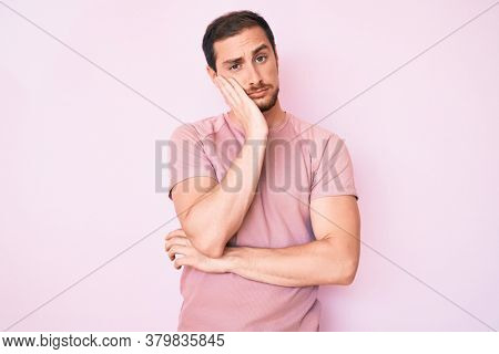 Young handsome man wearing casual tshirt thinking looking tired and bored with depression problems with crossed arms.