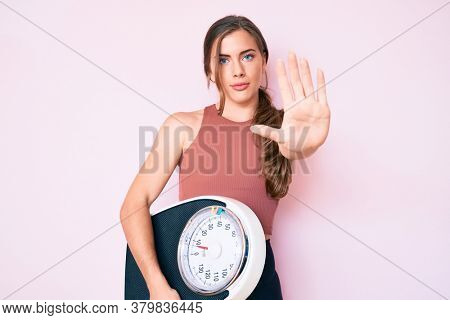 Beautiful young caucasian woman holding weight machine to balance weight loss with open hand doing stop sign with serious and confident expression, defense gesture