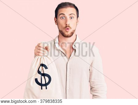 Young handsome caucasian man holding money bag with dollar symbol scared and amazed with open mouth for surprise, disbelief face