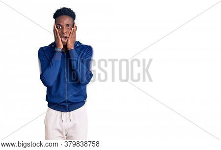 Young african american man wearing sportswear afraid and shocked, surprise and amazed expression with hands on face