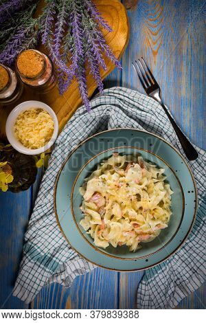 Tagliatelle Mosse Carbonara In Bowl On Wooden Table. Shallow Depth Of Field.