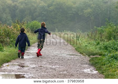 Two Brothers Splashing In Puddles