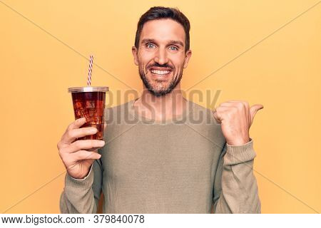 Young handsome man drinking cola refreshment beverage over isolated yellow background pointing thumb up to the side smiling happy with open mouth