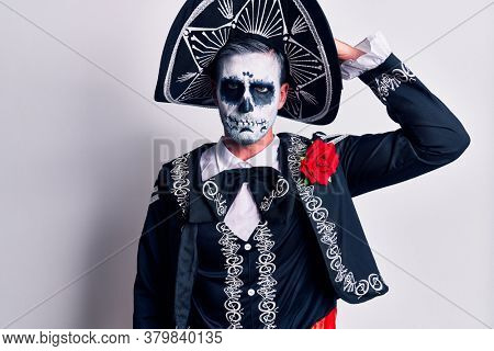 Young man wearing mexican day of the dead costume over white confuse and wonder about question. uncertain with doubt, thinking with hand on head. pensive concept.