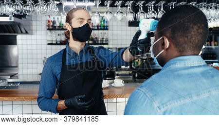 Caucasian Male Handsome Bartender In Mask And Gloves Measuring Temperature To African American Clien