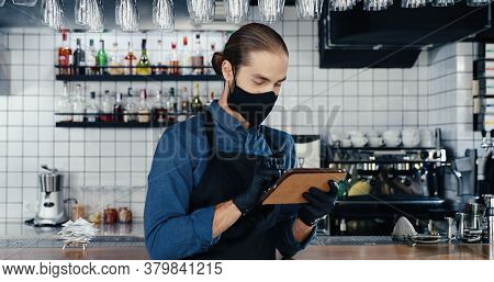 Male Caucasian Barmen In Mask, Gloves And Apron Using Tablet Device In Cafe At Kitchen. Handsome You