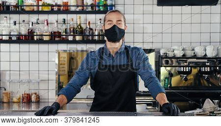 Portrait Shot Of Young Caucasian Handsome Man Barrista In Mask, Gloves And Apron In Cafe. Male Barma