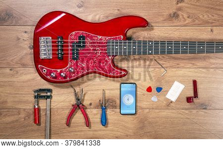 Luthier Table Top View With Bass Guitar And Tools. Craftsman Wooden Desk Flatlay View With Red Elect