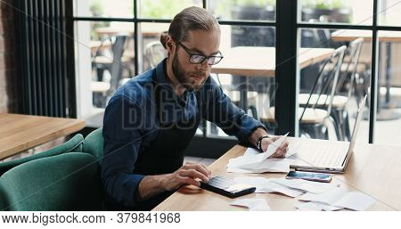 Caucasian Young Man Sitting At Table And Doing Business Calculations. Man In Glasses Calculating Spe