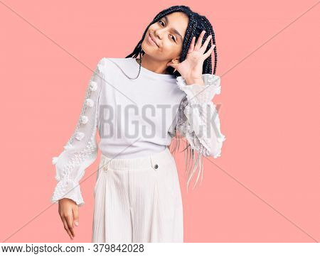 Cute african american girl wearing casual white tshirt smiling with hand over ear listening an hearing to rumor or gossip. deafness concept.