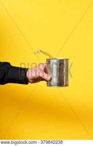 Man Holding A Can On Yellow Background