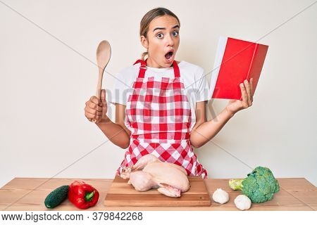 Young beautiful blonde woman wearing professional baker apron reading cooking recipe book afraid and shocked with surprise and amazed expression, fear and excited face.