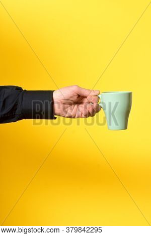 Man Holding A Mug On Yellow Background