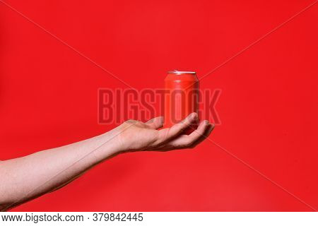 Man Holding A Can On Red Background