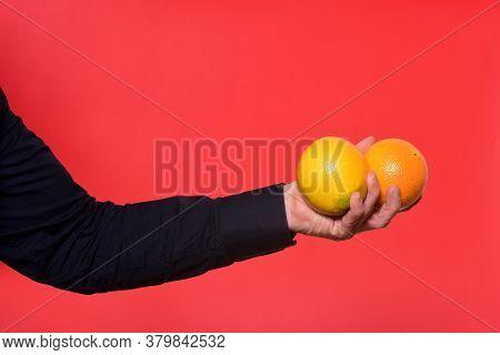 Hand Holding Two Orange Fruit On Red Background