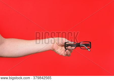 A Hand Holding A Glasses On Red