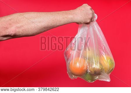Bag Of Plastic With Fruits On Red Background