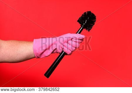 Hand With Glove Holding Brush On Red Background
