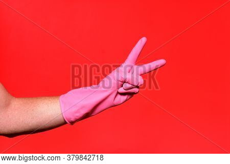 Hand With Glove And V Sign On Red Background