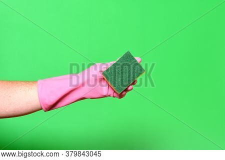 Hand With Glove Hoding Scourer On Green Background