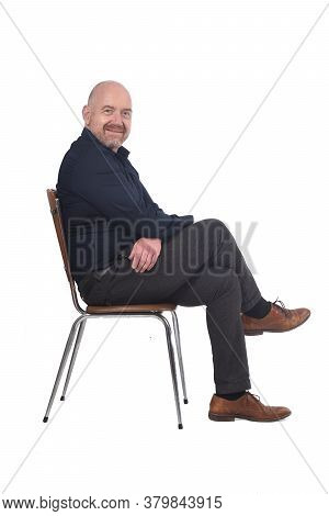 Portrait Of A Man Sitting On A Chair In White Background, Looking At Camera