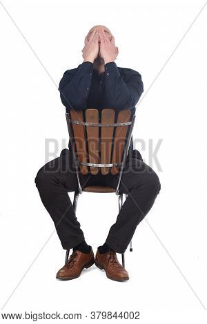Thoughtful Man Sitting On A Chair, Hands On Face