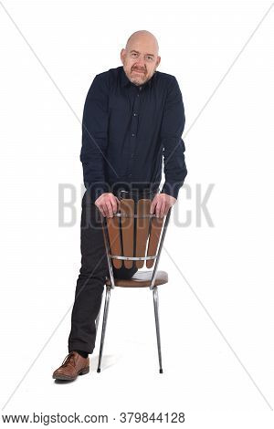 Man Standing With A Chair In White Background, Knees Over The Chair