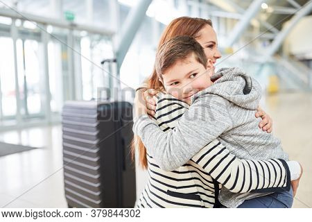 Son welcomes his mother on reunion after a trip in the airport terminal