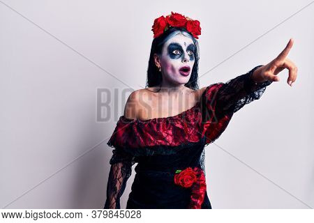 Young woman wearing mexican day of the dead makeup pointing with finger surprised ahead, open mouth amazed expression, something on the front