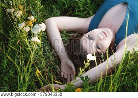 A Beautiful Blonde Woman In A Blue Long Dress Lies In A Field In Flowers. The Concept Of Beauty, Fre