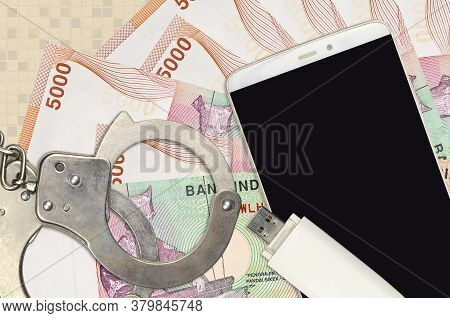 5000 Indonesian Rupiah Bills And Smartphone With Police Handcuffs. Concept Of Hackers Phishing Attac
