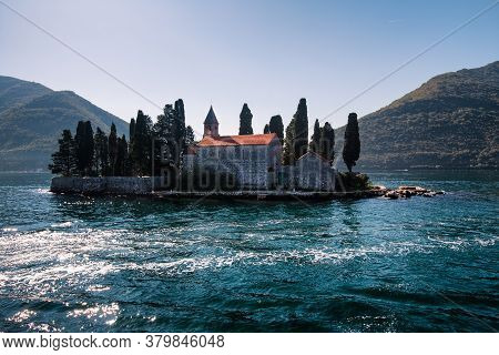 Catholic Red Roof Medieval Monastery, Bell Tower, Masonry Wall And Cypress Trees On An Island In The