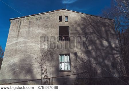 Young Man In A Dilapidated House Looks Out The Window