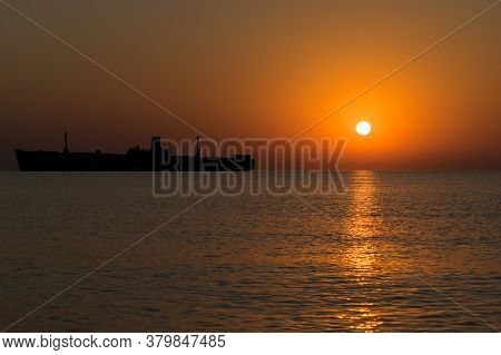 Shipwrecked. Beautiful Sunrise At Sea. The Silhouette Of An Abandoned Wreck In The Sea