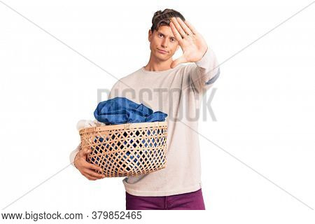 Young handsome man holding laundry basket with open hand doing stop sign with serious and confident expression, defense gesture