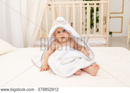 Baby Boy 8 Months Old Sitting On A White Bed In A White Towel After Bathing In The Bathroom At Home,