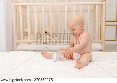 Smiling Baby Boy 8 Months Old Sitting In Diapers On A White Bed With A Bottle Of Milk At Home, Baby