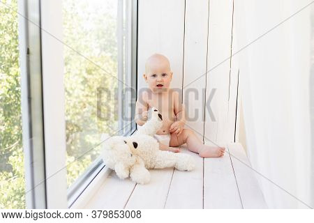 A Small Child A Boy Is Sitting In Diapers On The Window With Soft Toys Bears